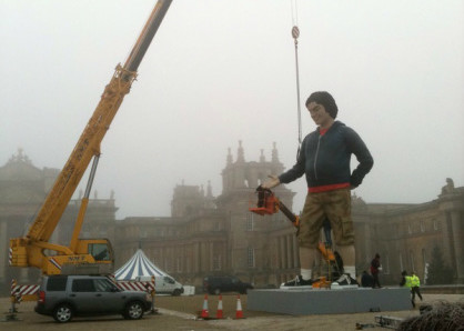 A picture of a crane lifting a statue