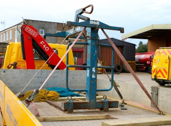 A lifting accessory strapped into the back of a truck