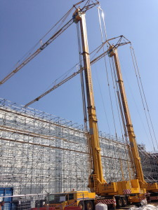 A picture of a pair of tower cranes working alongside each other on site