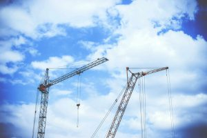 A picture of a crane hire with two cranes pictures before a sky line with blue sky and clouds.