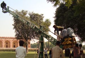An image of a film director using a crane to shoot a sequence of a movie