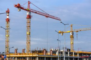 A picture of 3 tower cranes on an industrial park for hire