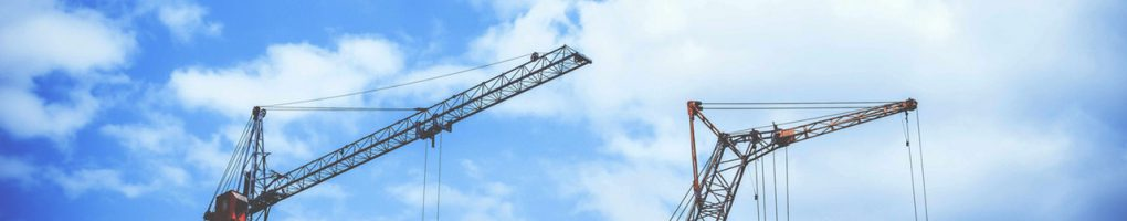 A picture of two tower cranes using their articulating jibs