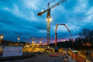 A picture of a construction site at night with cranes hire