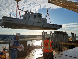 image of crane operator and signal person working to load a boat